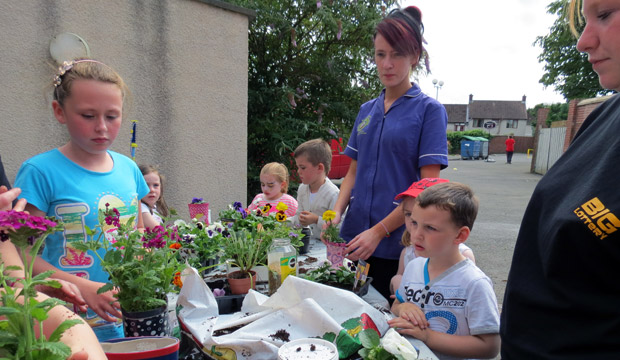 Children learning gardening skills with the team